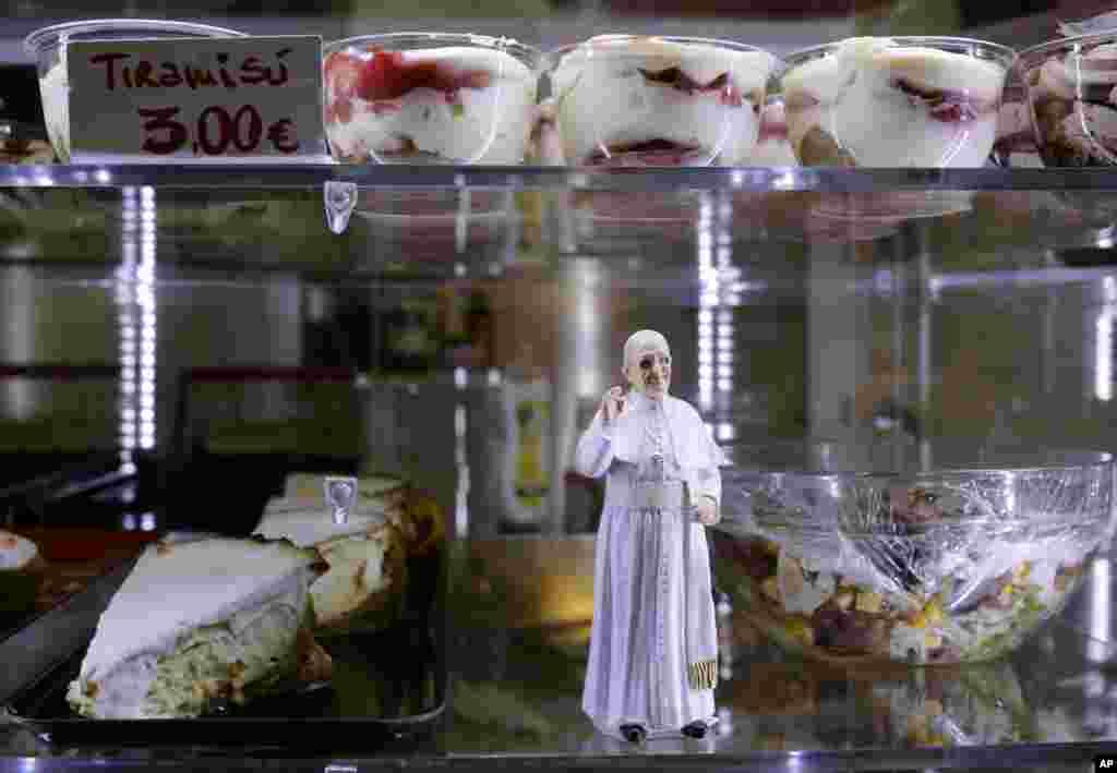 Patung Paus Fransiskus diletakkan di antara makanan pencuci mulut yang dijual di sebuah kafe, di Lapangan Santo Petrus di Vatikan, 27 April 2014.