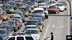 骑车人面对北京街头的汽车长龙