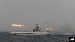 An Iranian navy boat fires a missile in a drill in the sea of Oman, December 30, 2011.