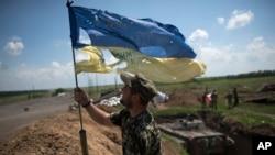 Український солдат встановлює прапор України на українських позиціях у Мар'їнці під Донецьком, 5 червня 2015