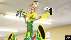 Alfred Baloyi, wearing a makarapa decorated with the image of South African football legend, Lucas Radebe, inside his factory in Johannesburg