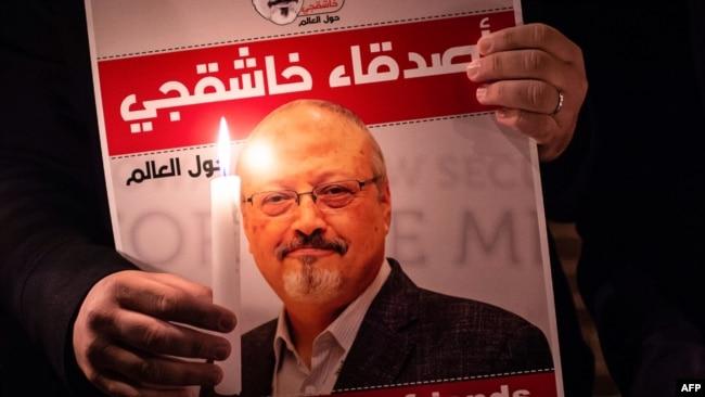 资料照片:一名抗议者在沙特驻伊斯坦布尔领事馆外举着卡舒吉的照片。(2018年10月25日)