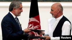 Kandidat-kandidat presiden Afghanistan Ashraf Ghani (kanan) dan Abdullah Abdullah menandatangani kesepakatan mengenai pembagian pemerintahan persatuan di Kabul (21/9). (Reuters/Omar Sobhani)