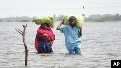 A couple carry their belongings as they wade through flood waters in the village of Ali Nawaz Khuso, Badin district of Pakistan's Sindh province, September 14, 2011.