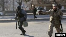 Cảnh sát Afghanistan chạy tới trụ sở cảnh sát giao thông bị tấn công ở Kabul, ngày 21/1/2013.