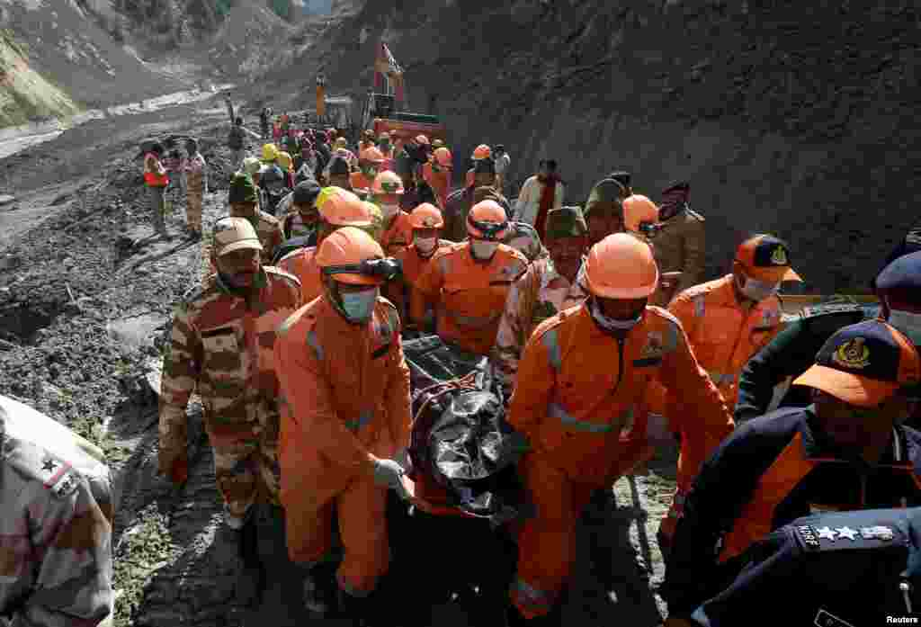 Members of National Disaster Response Force (NDRF) carry the body of a victim after recovering it during a rescue operation outside a tunnel after a part of a glacier broke away, in the northern state of Uttarakhand, India.