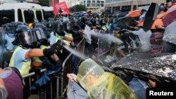 Cảnh sát chống bạo động xịt hơi cay trong lúc đụng độ với người biểu tình chặn con đường chính bên ngoài trụ sở chính quyền Hong Kong, ngày 28 tháng 9, 2014.