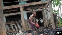 Cư dân thu nhặt các vật dụng còn sót lại tại một đền thờ Hồi giáo bị thiêu rụi tại làng Thabyu Chi trong bang Rakhine ở miền tây Miến Điện, ngày 2/10/2013.