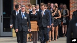 FILE - The casket of Otto Warmbier is carried from Wyoming High School after his funeral, June 22, 2017.