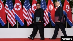 U.S. President Donald Trump and North Korea's leader Kim Jong Un walk during their summit at the Capella Hotel on Sentosa island in Singapore, June 12, 2018.