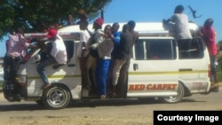 Some touts hanging on kombi windows in Chitungwiza on Tuesday following clashes between the police and kombi drivers. (Photo: Councillor Rangarirai Mutingwende)
