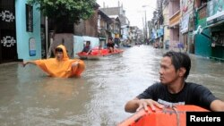 Residents wade through a flooded street during Tropical storm Fung-Wong in Pasay city, metro Manila, September 19, 2014.