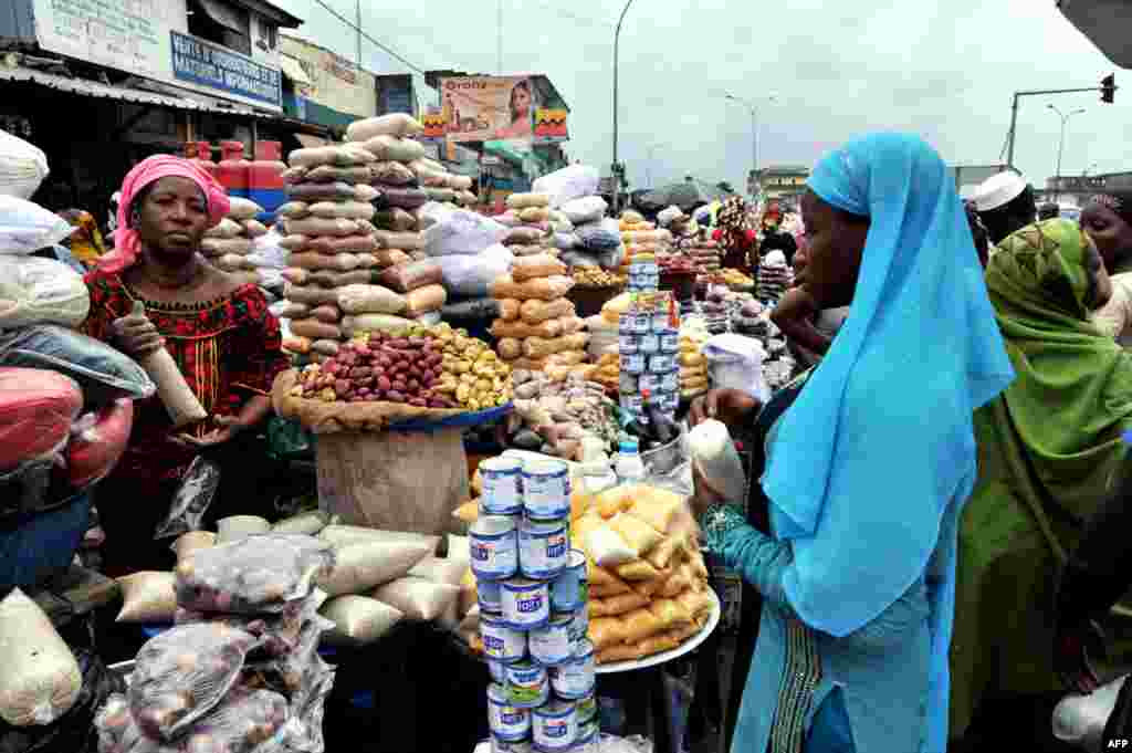 A woman shops for dates and cereals in a street market in Abobo, Ivory Coast, July 9, 2013.