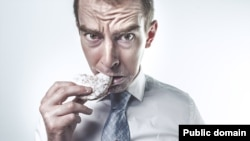stressed out man eating doughnut