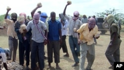 FILE - Participants of an execution by stoning are seen in Afgoye district, Somalia, Dec. 13, 2009. The al-Shabab militant group allegedly stoned to death a 44-year-old man in Rama Addey town in southern Somalia's Bay region, having found him guilty of adulter