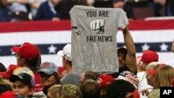 """ຊາຍສະໜັບສະໜຸນທ່ານທຣຳ ຜູ້ນຶ່ງ ໄດ້ໃສ່ເສື້ອ ທີເຊີດ ທີ່ອ່ານ ວ່າ """"ເຈົ້ານັ້ນລະ ແມ່ນຂ່າວປອມ"""" ຫຼືວ່າ """"You Are Fake News"""" ກ່ອນການໂຮມຊຸມນຸມ ໂດຍປະທານາທິບໍດີສະຫະລັດ ທ່ານດໍໂນລ ທຣຳ ໃນເມືອງໂຣແຈສເຕີຣ໌ ໃນລັດ ມິນີໂຊຕາ, ວັນທີ 4 ຕຸລາ 2018."""