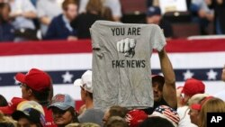 "FILE - A Trump supporter holds a T-shirt reading ""You Are Fake News"" before a rally by President Donald Trump in Rochester, Minn., Oct. 4, 2018. Freedom House says that democracy in the U.S. weakened significantly and partly blames U.S. President Donald Trump."