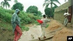 Quelques habitants du quartier d'Abobo traversent une planche sur le système de drainage inondé et le banc de sable construit pour protéger leur maison, à Abidjan, Côte d'Ivoire, 2 juin 1998.
