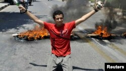 A protester carries stones in one hand and a beer bottle in the other as he kneels in front of burning tires set by protesters in front of Luxor governorate building to protest against the newly-appointed governor, Adel Mohamed al-Khayat in Luxor, Egypt, June 19, 2013.