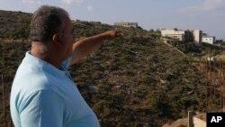 23일 레바논에서 한 남성이 이스라엘의 공습을 받은 반군 기지를 가리키고 있다.