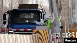 身穿防護服的警察在河北省合格北京的一個道路檢查站攔住卡車卡車。(2021年1月12日)