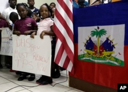 Children stand next to United States and Haitian flags as they hold signs in support of renewing Temporary Protected Status (TPS) for immigrants from Central America and Haiti now living in the United States, during a news conference, Nov. 6, 2017, in Mia