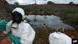 Waste removal experts work to extract hazardous black sludge from a garbage dump in Abidjan, Ivory Coast, September 17, 2006. (AP)