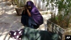 Asha et Muna attendent assistance en dehors du bureau du HCR à la ville de Galkayo. Muna, dort sur le sol parce qu'elle ne pouvait pas résister à la douleur à la cuisse. Elle a été poignardée par un violeur le 26 novembre de 2010.