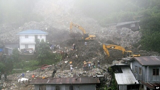Rescuers and volunteers try to clear piles of garbage under thick fog in Baguio City, northern Philippines, August 29, 2011