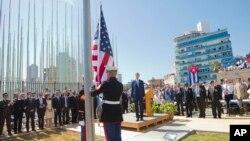 Menteri Luar Negeri AS John Kerry dan para pejabat lainnya menyaksikan penaikan bendera oleh para marinir di Kedutaan Besar AS di Havana, Kuba (14/8).
