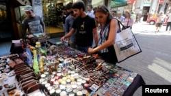 People look at marijuana smoking paraphernalia in a street market in downtown Montevideo, March 10, 2014.
