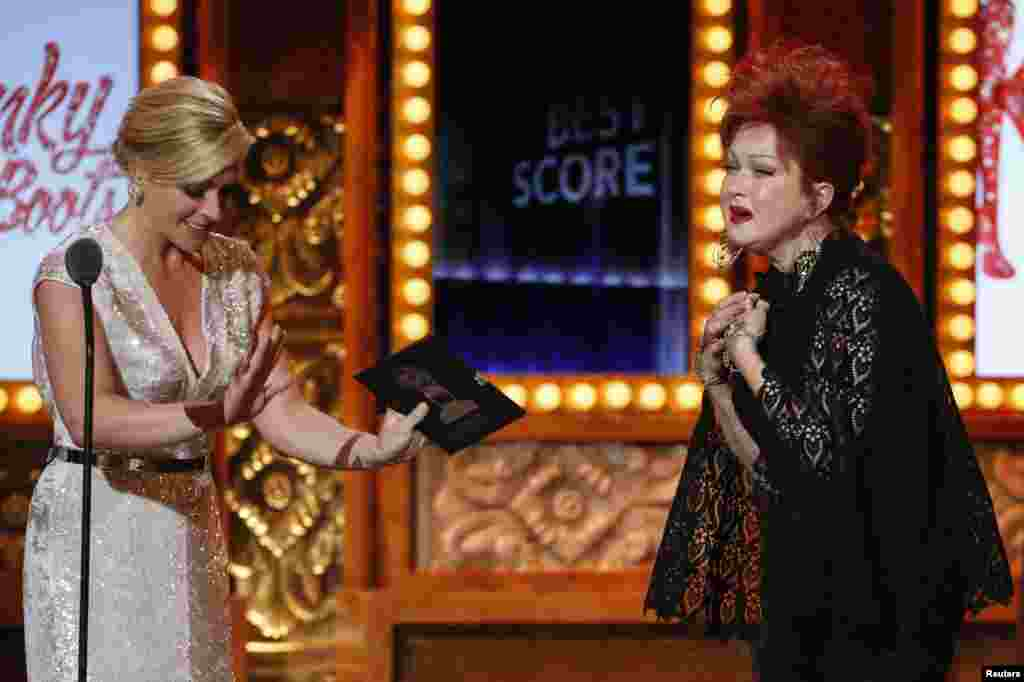 "Cyndi Lauper enters the stage to accept the award for Best Original Score (Music and/or Lyrics) Written for the Theatre for ""Kinky Boots"" from Jane Krakowski during the Tony Awards in New York, June 9, 2013."