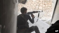 FILE - This undated photo posted Nov. 4, 2014 by the Raqqa Media Office of the Islamic State group - a militant extremist group, shows an Islamic state group fighter in Kobani, Syria.