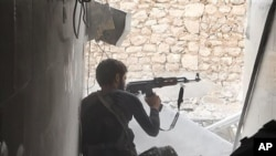 FILE - An Islamic state group fighter in Kobani, FILE - An Islamic State fighter in Kobani, Syria.