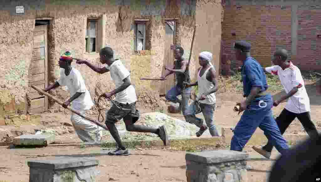 Members of the Imbonerakure pro-government youth militia chase after opposition protesters, unhindered by police, in the Kinama district of the capital Bujumbura, May 25, 2015.