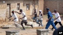 FILE - Members of the Imbonerakure pro-government youth militia chase after opposition protesters, unhindered by police, in the Kinama district of the capital Bujumbura, Burundi on May 25, 2015.