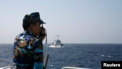 FILE - An officer of the Vietnamese coast guard officer speaks on a radio as he monitors a Chinese vessel in the South China Sea. Along with fishing and lucrative shipping routes, oil and gas reserves are often cited as a major reason for the disagreements over which country owns which patch of water.