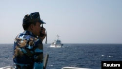 Vietnamese coast guard officer monitors Chinese vessel in the South China Sea, about 210 km (130 miles) off coastal Vietnam, May 15, 2014.