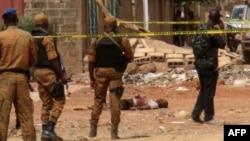 Des éléments forces de sécurité burkinabè se tiennent près du corps d'un suspect jihadiste abattu à Ouagadougou, le 22 mai 2018.