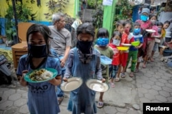 Locals wearing protective masks carry plates while queueing for food distributed for free amid the spread of coronavirus disease (COVID-19) in Bandung, West Java province, Indonesia, April 10, 2920..