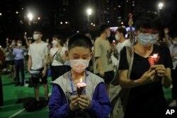 香港维多利亚公园参加六四31周年悼念活动的人手持蜡烛。(2020年6月4日)