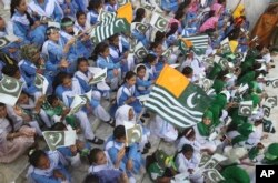 Pakistani students wave Pakistani and Kashmiri flags at the mausoleum of Muhammad Ali Jinnah, founder of Pakistan, to celebrate the Independence Day in Karachi, Pakistan, Aug. 14, 2019.