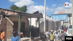 Grupos de haitianos observan los destrozos causados por un fuerte terremoto de magnitud 7,0 en el oriente del país el 14 de agosto de 2021. Foto de Makenson Charles, VOA.