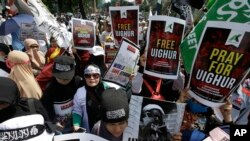 """Muslim protesters rally outside China's embassy in Jakarta, Indonesia, Friday, Dec. 21, 2018. Several hundred protesters chanted """"God is Great"""" and """"Get out, communist!"""" outside China's embassy in the Indonesian capital."""