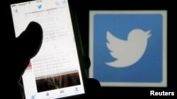 FILE - A man reads tweets on his phone in front of a displayed Twitter logo in Bordeaux, southwestern France, March 10, 2016.
