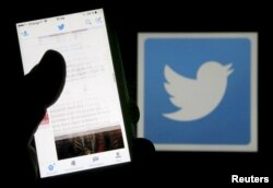 FILE - A man reads tweets on his phone in front of a displayed Twitter logo, March 10, 2016.
