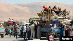 Syrian refugees, fleeing the recent fighting in Arsal, wait by trucks in the Bekaa valley, near the Lebanese border with Syria.