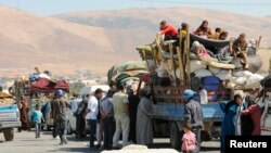 Syrian refugees, fleeing the recent fighting in Arsal, wait by trucks in the Bekaa valley, near the Lebanese border with Syria, Aug. 8, 2014.