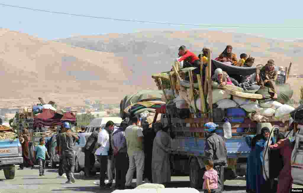 Syrian refugees, fleeing the recent fighting in Arsal, wait by trucks in Majdel Anjar in the Bekaa valley, near the Lebanese border with Syria. The refugees, who had sought shelter in Arsal, were attempting to head back to Syria; however, they say Syrian authorities at the border rejected them until further investigation to verify their identities and statuses.