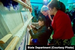 Kerry, center, examines weaving of a traditional silk carpet at Registan in Samarkand, Uzbekistan, spotlighting the importance of cultural preservation, Nov. 1, 2015.
